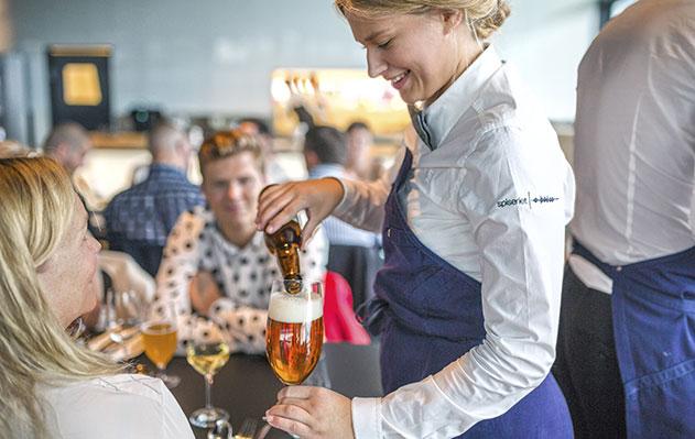 Arrangement. Servitør skjenker drikke i glass.
